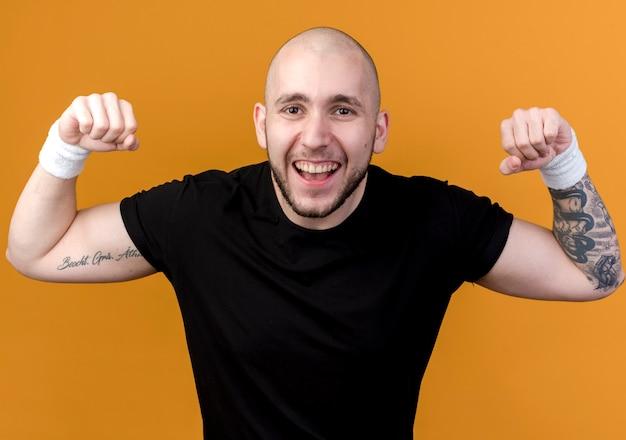 Vrolijke jonge sportieve man met polsbandje doet sterk gebaar geïsoleerd op een oranje achtergrond