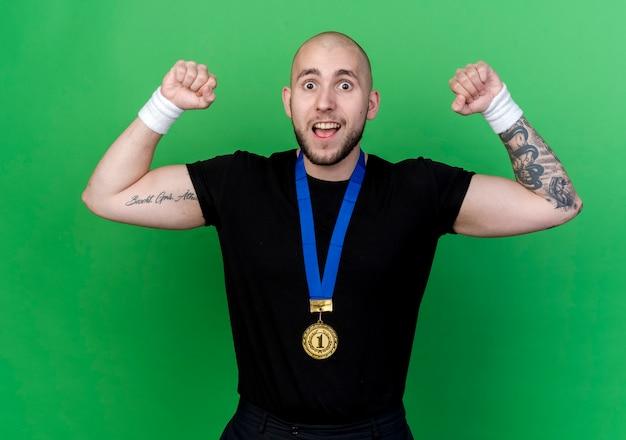 Vrolijke jonge sportieve man met polsbandje en medaille doet sterk gebaar