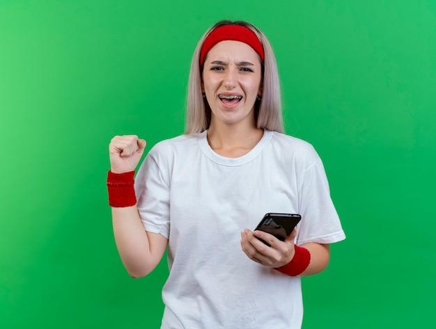 Vrolijke jonge sportieve vrouw met beugels met hoofdband en polsbandjes houdt vuist en houdt telefoon geïsoleerd op groene muur