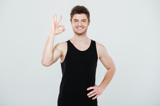 Vrolijke jonge sportman die ok gebaar toont.