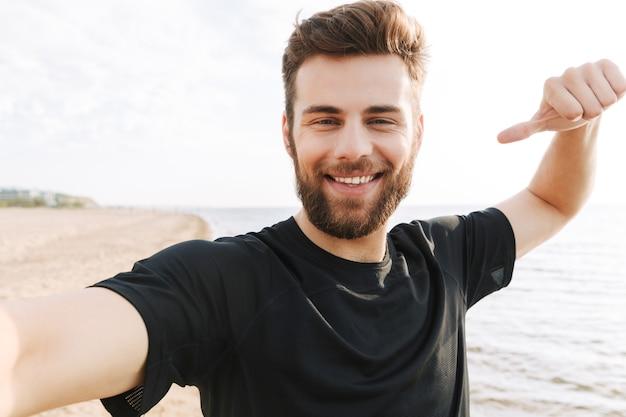 Vrolijke jonge sportman met koptelefoon die een selfie neemt