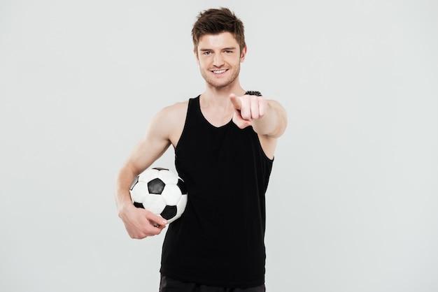 Vrolijke jonge sportman met voetbal staande geïsoleerd op witte achtergrond. kijkend naar camera wijzen.