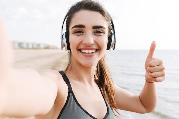 Vrolijke jonge sportvrouw met hoofdtelefoons