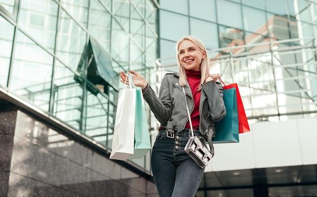 Vrolijke jonge stijlvolle vrouwelijke shopper met kleurrijke boodschappentassen met aankopen en gelukkig lachend tijdens een wandeling in de buurt van modern winkelcentrum op straat in de stad