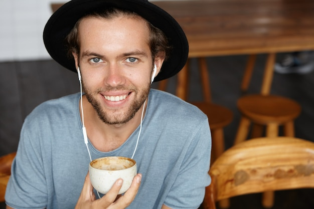 Vrolijke jonge student in casual t-shirt en trendy hoed luisteren naar nieuw album van zijn favoriete artiest op oortelefoons, met behulp van online muziek-app op mobiele telefoon
