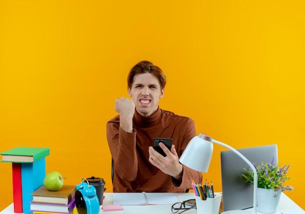 Vrolijke jonge studentenjongen die aan bureau met schoolhulpmiddelen zit die telefoon houden en ja gebaar tonen