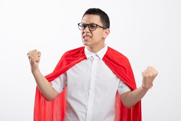 Vrolijke jonge superheld jongen in rode cape bril doen ja gebaar kijken kant geïsoleerd op een witte achtergrond