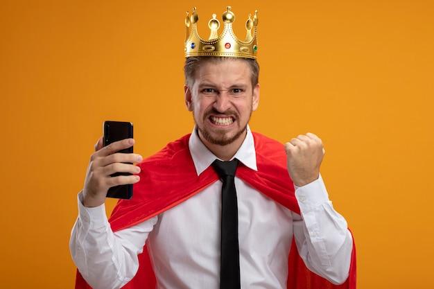 Vrolijke jonge superheld kerel die stropdas en kroon draagt ?? die telefoon houdt en ja gebaar toont dat op oranje achtergrond wordt geïsoleerd