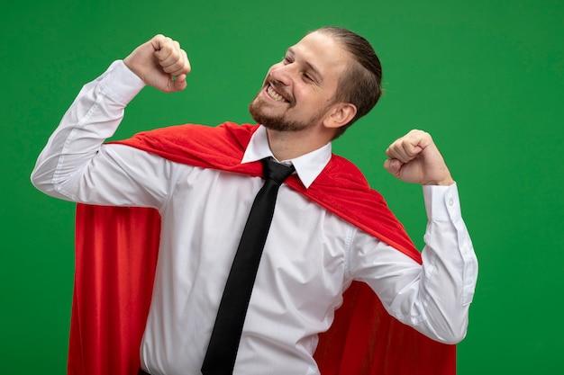 Vrolijke jonge superheld kerel kijken naar kant tonen ja gebaar geïsoleerd op groene achtergrond