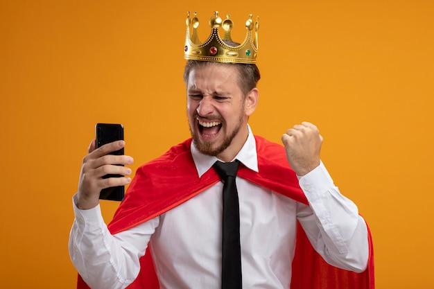 Vrolijke jonge superheld man dragen stropdas en kroon houden en kijken naar telefoon weergegeven: ja gebaar geïsoleerd op een oranje achtergrond