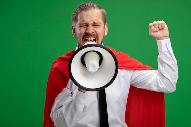 Vrolijke jonge superheld man spreekt op loudspeakes en heft vuist geïsoleerd op groene achtergrond