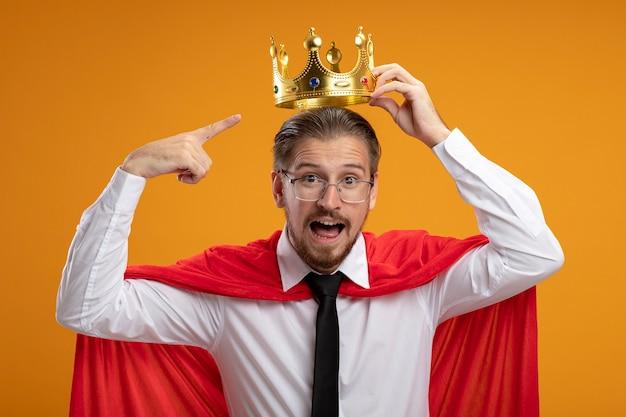 Vrolijke jonge superheld man stropdas en bril zetten kroon op hoofd geïsoleerd op een oranje achtergrond