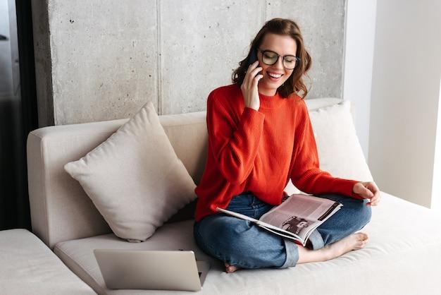 Vrolijke jonge terloops geklede vrouw in koptelefoon zittend op een bank thuis, studeren met laptopcomputer, mobiele telefoon te houden
