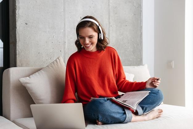 Vrolijke jonge terloops geklede vrouw in koptelefoon zittend op een bank thuis, studeren met laptopcomputer