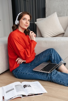 Vrolijke jonge terloops geklede vrouw in koptelefoon zittend op een vloer thuis, studeren met laptopcomputer