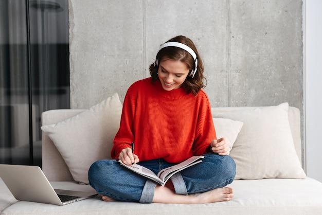 Vrolijke jonge terloops geklede vrouw zittend op een bank thuis, studeren met laptop