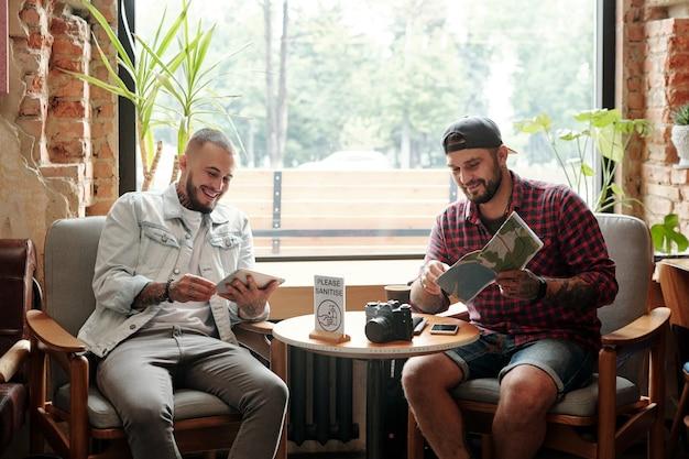 Vrolijke jonge toeristen zitten tegen raam en plannen reisroute met behulp van online en papieren kaarten