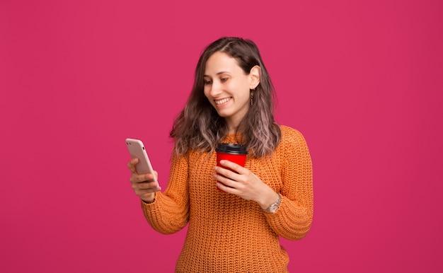Vrolijke jonge trendy vrouw die haar smartphone bekijkt en kop van koffie houdt