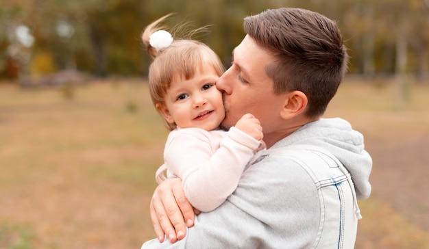 Vrolijke jonge vader die zijn kleine schattige dochter buiten kust