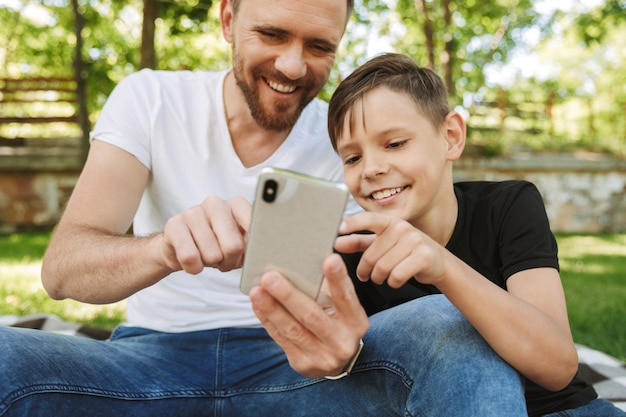 Vrolijke jonge vader zit met zijn zoontje met behulp van mobiele telefoon.