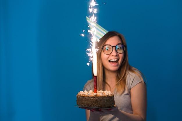 Vrolijke jonge vage studente die in glazen een felicitatietaart met een kaars staande houden