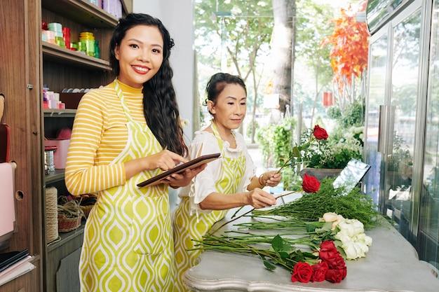 Vrolijke jonge vietnamese bloemenwinkeleigenaar die vragen van klant beantwoordt via toepassing op digitale tablet wanneer bloemist boeket maakt