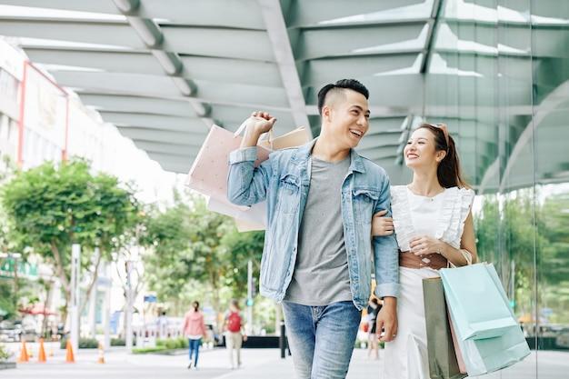 Vrolijke jonge vietnamese paar wandelen in de straat na het winkelen in winkelcentrum in het weekend