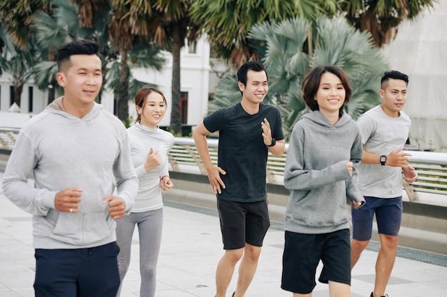 Vrolijke jonge vietnamese studenten die 's ochtends buiten joggen