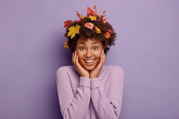 Vrolijke jonge volwassen vrouw met herfstbladeren in haar, kijkt direct naar camera met aangename glimlach, draagt paarse gebreide trui, heeft een vrolijke seizoensstemming