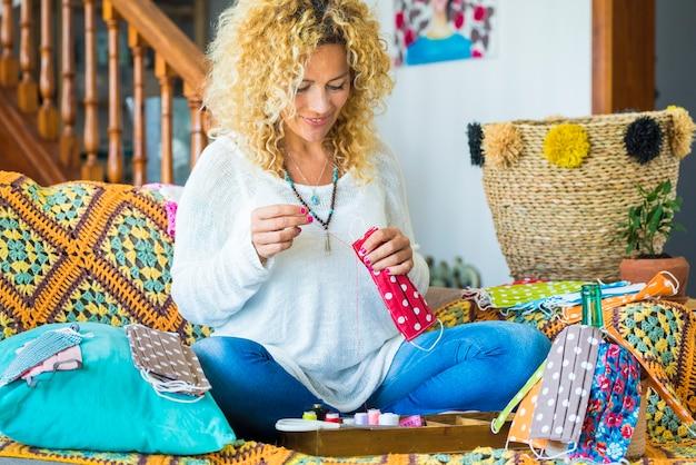 Vrolijke jonge volwassen vrouwelijke mensen werken thuis en produceren trendy kleurrijke coronavirusmaskers om te beschermen tegen covid