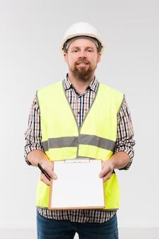 Vrolijke jonge voorman die klembord met notities op papier toont terwijl hij voor de camera staat
