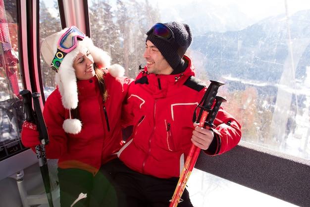 Vrolijke jonge vrienden op skilift rijden omhoog op besneeuwde berg