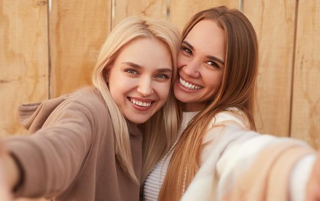 Vrolijke jonge vriendinnen in warme gebreide kleding omarmen en lachen terwijl het nemen van selfie samen tegen houten muur