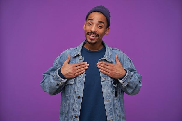 Vrolijke jonge vrij donkere bebaarde man in blauwe pet, trui en spijkerbroek jas kijkt positief met een brede, oprechte glimlach, staande over paarse muur met handen op zijn borst