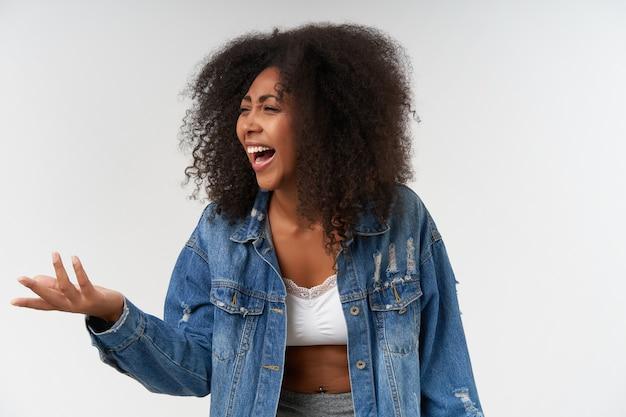Vrolijke jonge, vrij donkere vrouw met krullend haar die opzij kijkt en handpalm omhoog houdt, fronsend gezicht en vrolijk lacht om grappige grap, poserend over witte muur