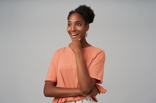 Vrolijke jonge vrij gekrulde brunettened vrouw die haar kin met opgeheven hand vasthoudt en breed lacht terwijl ze in vrijetijdskleding over grijze muur staat
