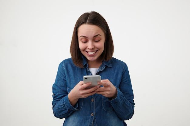 Vrolijke jonge vrij kortharige brunette dame met natuurlijke make-up haar mobiele telefoon in opgeheven handen houden en gelukkig lachend tijdens het kijken naar scherm, poseren op witte achtergrond