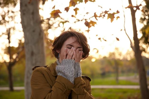 Vrolijke jonge vrij kortharige brunette vrouw die haar gezicht bedekt met opgeheven handpalmen terwijl ze gelukkig lacht, stijlvolle warme kleding draagt tijdens het wandelen over vergeelde bomen in de stadstuin