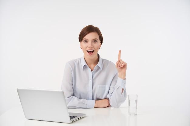 Vrolijke jonge vrij kortharige brunette vrouw met casual kapsel zittend op wit en naar boven tonen met opgeheven wijsvinger, vrolijk op zoek met brede mond geopend