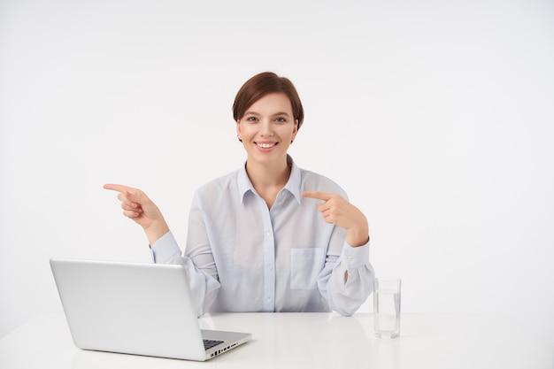 Vrolijke jonge vrij kortharige brunette vrouw werkt in kantoor met haar laptop en kijkt positief met brede glimlach, opzij poiting met wijsvingers zittend op wit