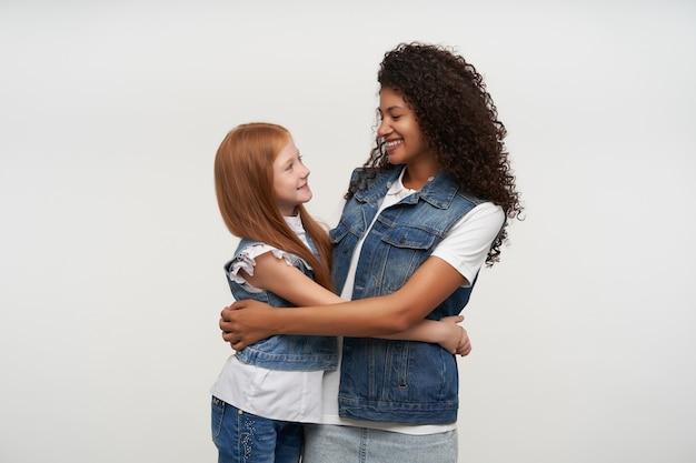 Vrolijke jonge vrij langharige meisjes die gelukkig op elkaar kijken en breed glimlachen, omarmen terwijl ze poseren op wit in spijkerbroek vesten en witte shirts