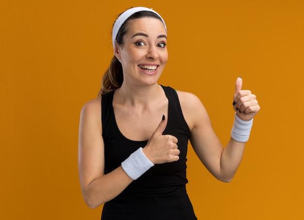 Vrolijke jonge vrij sportieve vrouw die hoofdband en polsbandjes draagt en naar de voorkant kijkt met duimen omhoog geïsoleerd op een oranje muur met kopieerruimte