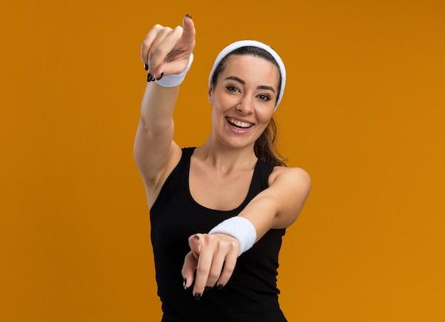 Vrolijke jonge, vrij sportieve vrouw met een hoofdband en polsbandjes die naar de voorkant kijkt en je gebaar maakt geïsoleerd op een oranje muur met kopieerruimte