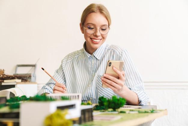 Vrolijke jonge vrouw architect die mobiele telefoon gebruikt tijdens het ontwerpen van concept met huismodel op de werkplek