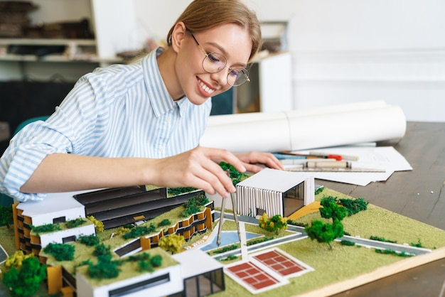 Vrolijke jonge vrouw architect in brillen ontwerpen ontwerp met huismodel en zittend op de werkplek