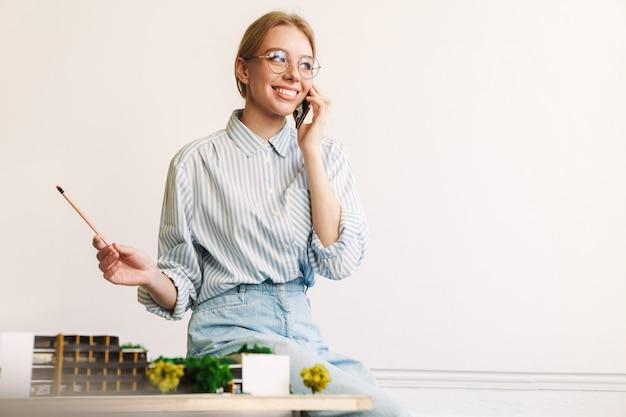 Vrolijke jonge vrouw architect praten op mobiele telefoon tijdens het ontwerpen van concept met huismodel op de werkplek