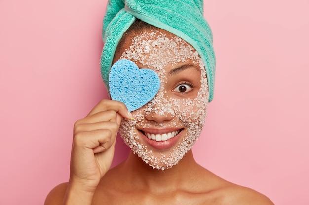 Vrolijke jonge vrouw bedekt één oog met een hartvormige cosmetische spons, verwijdert make-up, heeft zeezout scrub rond gezicht, tedere glimlach
