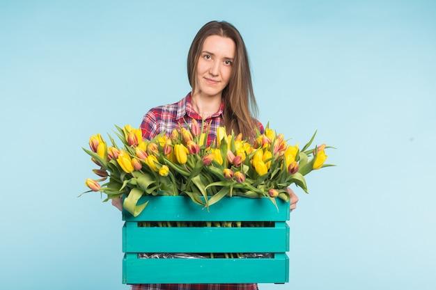 Vrolijke jonge vrouw bloemist houden doos tulpen.