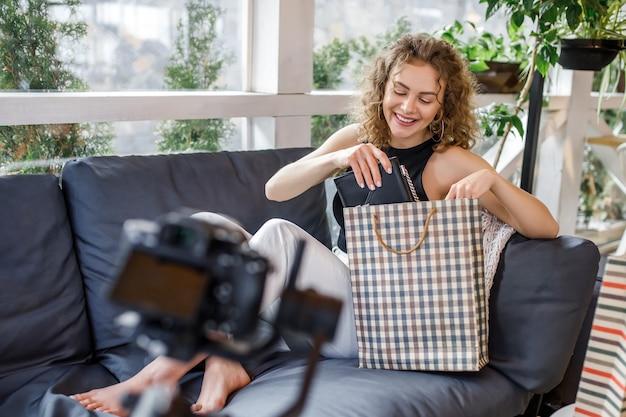 Vrolijke jonge vrouw blogger tijdens fashion blog, met tassen na het winkelen