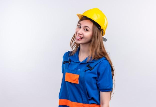 Vrolijke jonge vrouw bouwer werknemer in uniforme bouw en veiligheidshelm tong uitsteekt